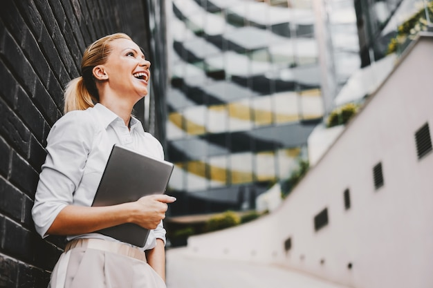 Smiling attractive blond fashionable businesswoman standing outdoors and holding tablet in her arms. business center exterior.