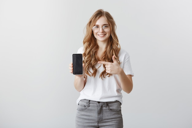 Smiling attractive blond girl in glasses pointing finger at smartphone screen, showing application