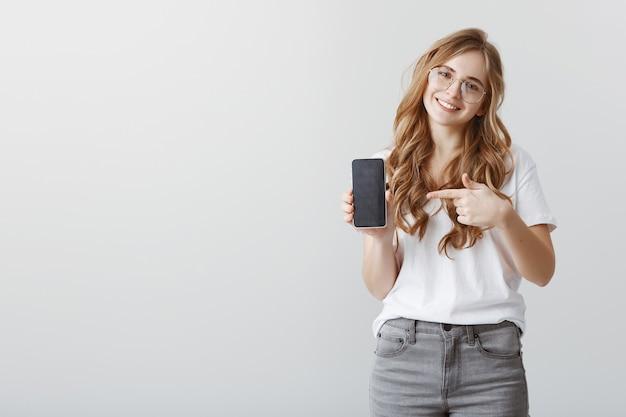 Улыбающаяся привлекательная блондинка в очках, указывая пальцем на экран мобильного телефона, показывая приложение