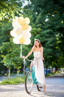 Smiling attractive brunette holding ballons while driving blue bike on park alley.