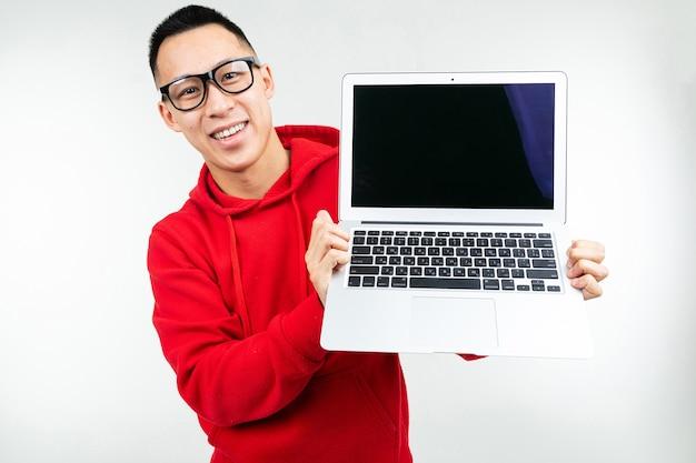 웃는 매력적인 갈색 머리 남자는 흰색 스튜디오 배경에 그의 손에 모형과 빈 노트북 화면을 보여줍니다.