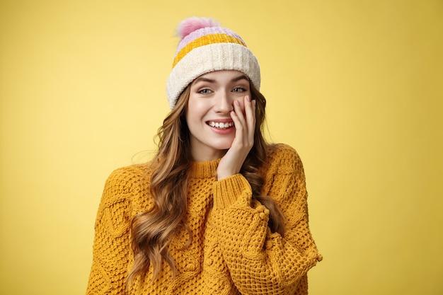 笑顔の魅力的なのんきな若い20代の女性は、カジュアルに話すのを楽しんでいます素敵な会話ガールフレンドプレス手のひらの頬面白がって赤面は軽薄な褒め言葉を受け取り、肯定的な黄色の背景に立っています