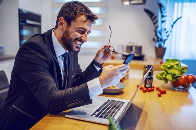 ダイニングテーブルに座っているとスマートフォンを使用してメッセージを読んだり送信したりするスーツの魅力的な白人実業家の笑みを浮かべてください。テーブルの上にはラップトップ、皿、野菜があります。