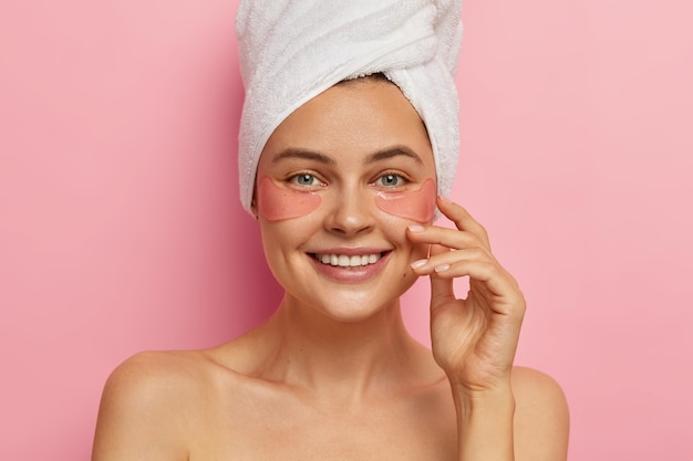 Smiling attractive european woman with glad face expression, wears pink silicone pads under eyes, happy to look fresh after shower and spa treatments, shows effect of perfect skin