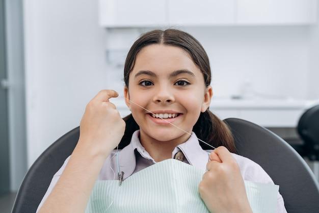 デンタルフロスを持っている笑顔で魅力的な女の子。歯科医の女の子、歯科治療