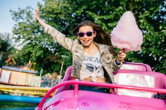 Smiling attractive girl in sunglasses riding a children's roller coaster