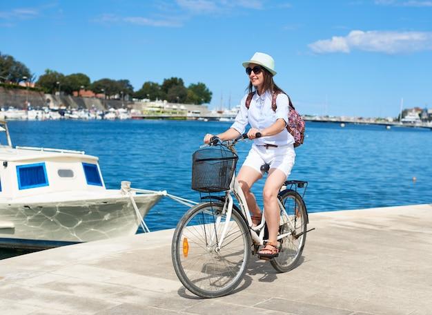 Улыбающаяся привлекательная девушка, едущая на городском велосипеде по каменистому тротуару, стоящая на якоре в уютной гавани темно-синяя круизная лодка