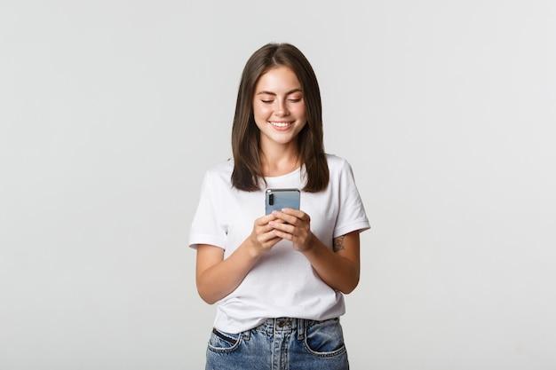 携帯電話を使用して魅力的な女の子の笑顔と画面を見て満足しています。