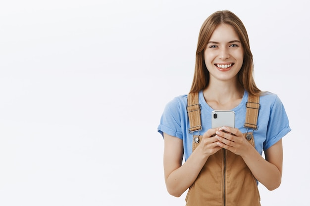 携帯電話、テキストメッセージ、またはソーシャルネットワークの閲覧を使用して魅力的な女の子を笑顔