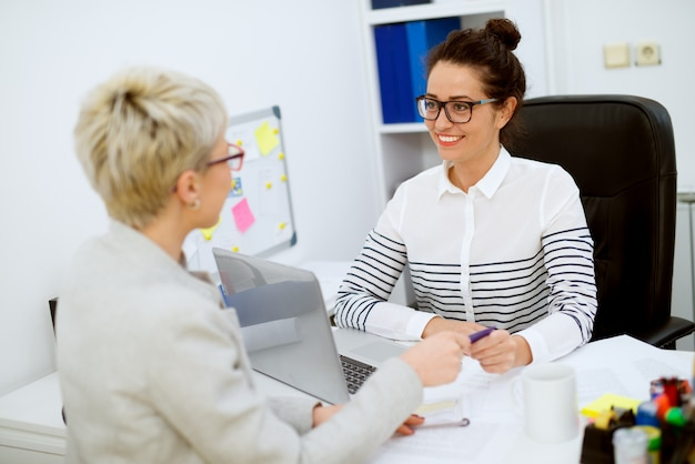 Smiling attractive middle aged successful financial assistant woman with eyeglasses sitting in front of the woman customer and taking a bank card in the office.