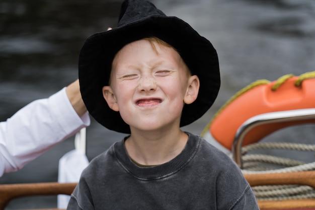 Улыбаясь привлекательный рыжий мальчик на яхте.