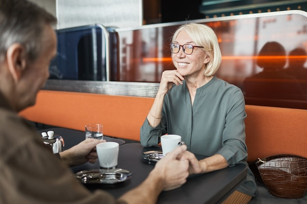 Smiling attractive senior caucasian woman in eyeglasses sitting at table in bistro cafe and holding hand of boyfriend while listening to him