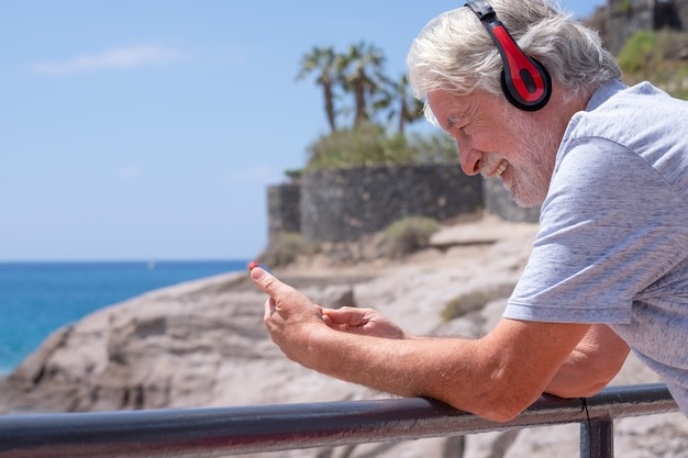 Smiling attractive senior man using mobile phone at the sea, wearing red headphones. happy retirement. horizon over the water