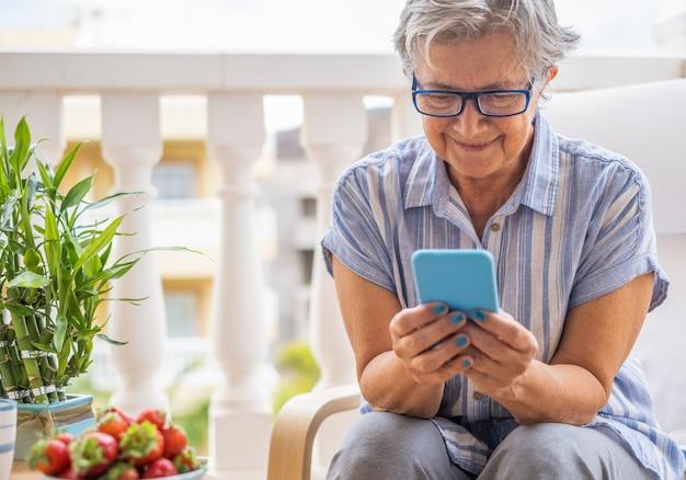 Улыбается привлекательная старшая женщина, сидящая на открытом воздухе на балконе, держа смартфон, отправляя сообщение. пожилая женщина, наслаждающаяся технологиями и социальными сетями