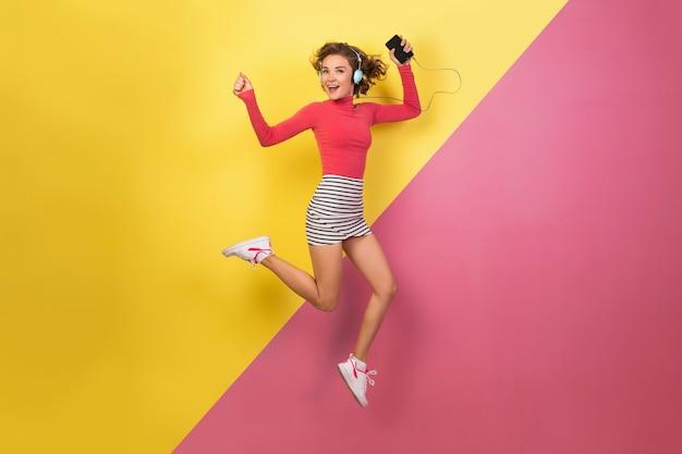 Улыбающаяся привлекательная улыбающаяся возбужденная женщина в стильной красочной одежде прыгает и слушает музыку в наушниках на розово-желтом фоне, модная летняя тенденция
