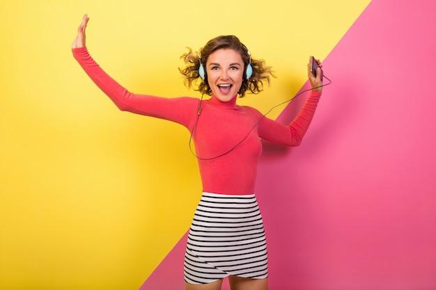 Donna eccitata sorridente attraente sorridente in vestito variopinto alla moda ballare e ascoltare musica in cuffia su sfondo giallo rosa, tendenza estate moda