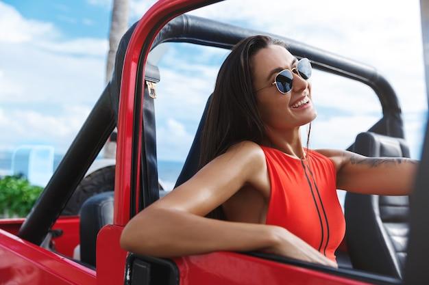 Sorridente attraente donna abbronzata in un costume da bagno rosso alla guida di un'auto.