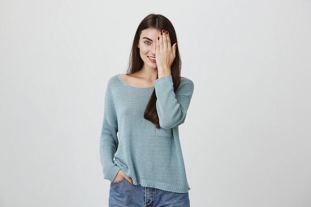 La donna attraente sorridente copre la metà del fronte di palma