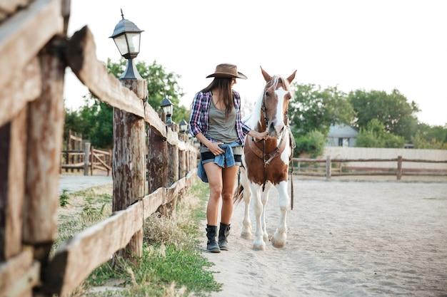 목장에서 그녀의 말과 함께 걷고 웃는 매력적인 여성 카우걸