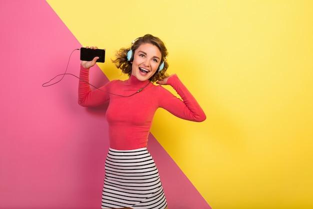 Улыбающаяся привлекательная женщина в стильном красочном наряде танцует и слушает музыку в наушниках