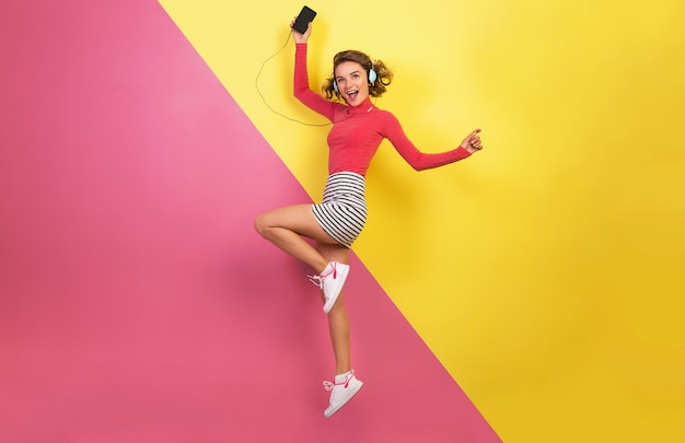 Улыбающаяся привлекательная женщина в стильном красочном наряде прыгает и слушает музыку в наушниках