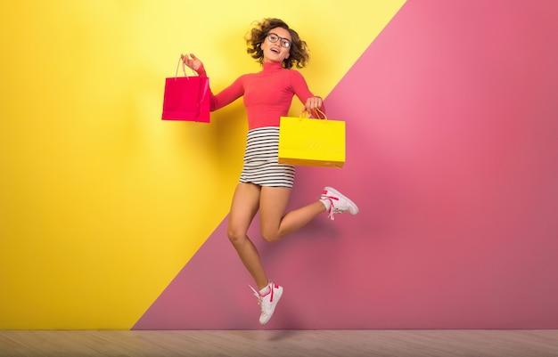 ピンクイエローバックグラウンド、ポロネック、ストライプミニスカート、買い物中毒、ファッション夏のトレンドのショッピングバッグでジャンプスタイリッシュなカラフルな衣装で魅力的な女性を笑顔