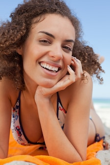 Smiling attractive woman lying down with hand on cheek