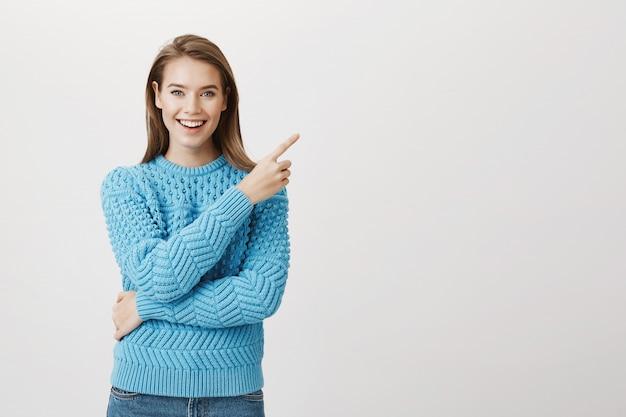 Donna attraente sorridente che indica il dito nell'angolo in alto a destra