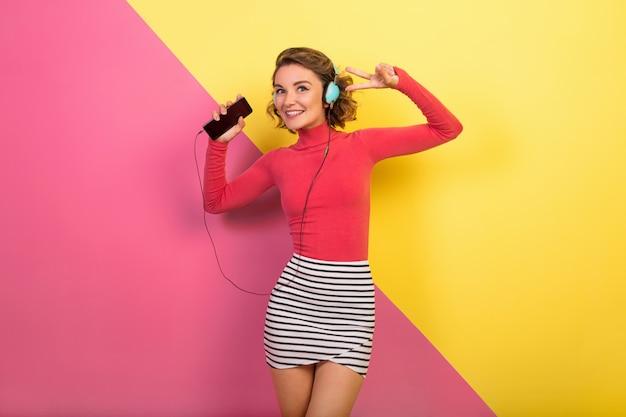 Donna attraente sorridente in vestito colorato alla moda ballare e ascoltare musica in cuffia
