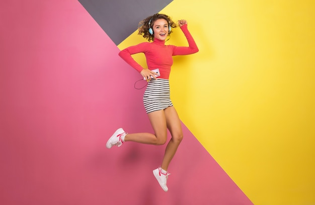 Smiling attractive woman in stylish colorful outfit jumping and listening to music in headphones