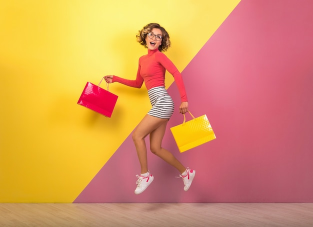 Smiling attractive woman in stylish colorful outfit jumping with shopping bags on pink yellow background, polo neck, striped mini skirt, shopaholic on sale, fashion summer trend
