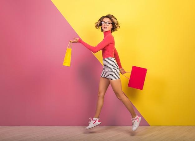 Donna attraente sorridente in vestito colorato elegante che salta con le borse della spesa su sfondo rosa giallo, collo a polo, minigonna a righe, shopaholic in vendita, tendenza estate moda
