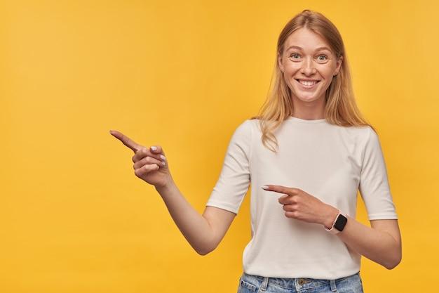 Улыбающаяся привлекательная женщина с веснушками в белой футболке, указывая двумя пальцами на обеих руках в пустое пространство на желтом