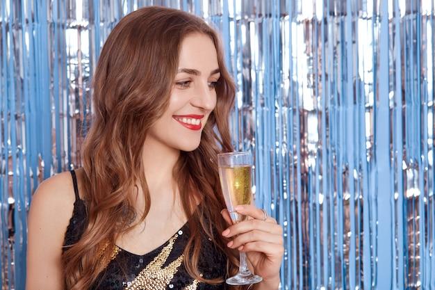 Улыбающаяся привлекательная женщина с красными губами, держащая в руках бокал вина или шампанского, смотрит в сторону с задумчивым и счастливым выражением лица у стены, украшенной серебряной мишурой.