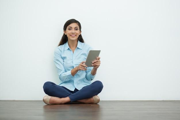 Улыбаясь привлекательная женщина с планшета на полу