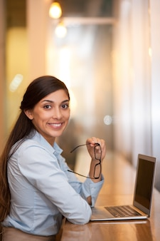 Smiling attractive woman working on laptop in cafe