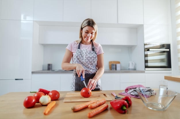 Smiling attractive worthy caucasian blonde woman in apron cutting tomato while standing in kitchen. on kitchen counter are carrots, tomatoes and peppers.