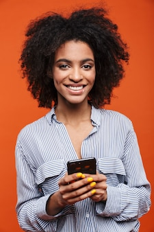 Smiling attractive young african woman using mobile phone isolated over red wall