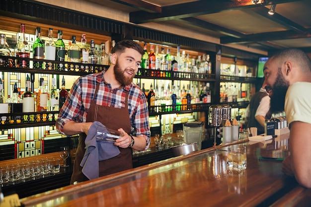 Улыбающийся привлекательный молодой бармен протирает очки и разговаривает с молодым человеком в баре