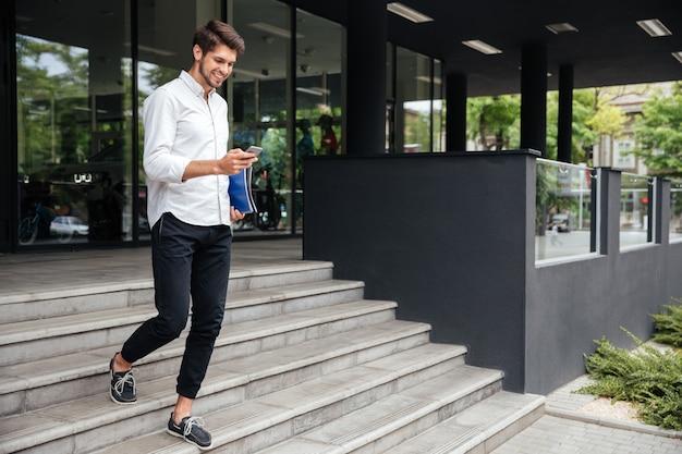 웃고 있는 매력적인 젊은 사업가가 비즈니스 센터 근처에서 걷고 휴대전화를 사용합니다.