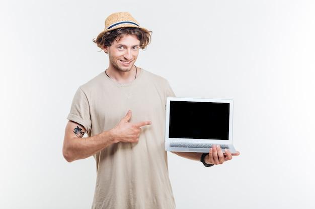 빈 화면 노트북을 들고 흰색 배경 위에 가리키는 웃는 매력적인 젊은 남자