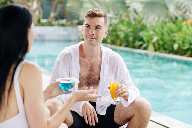 Smiling attractive young man spending time by swimming pool with girlfriend, talking and drinking cocktails