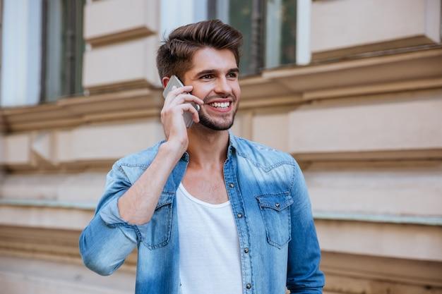 Улыбающийся привлекательный молодой человек стоит на улице и разговаривает по мобильному телефону