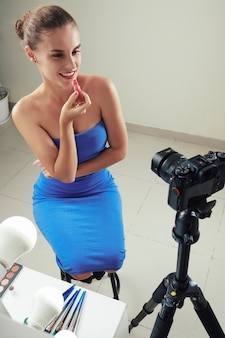 Smiling attractive young woman in blue tight dress sitting on stool in front of camera and applying lip gloss while shooting vlog