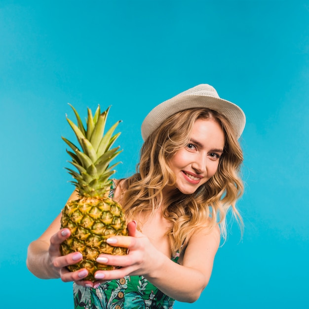 Smiling attractive young woman in hat holding fresh pineapple