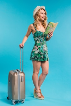 Smiling attractive young woman in hat holding map and suitcase