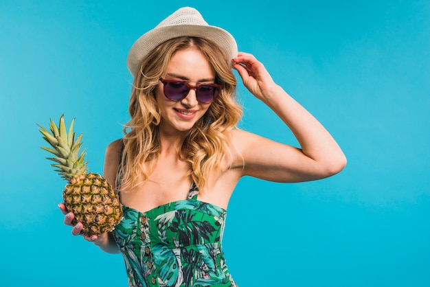 Smiling attractive young woman in hat and sunglasses holding pineapple