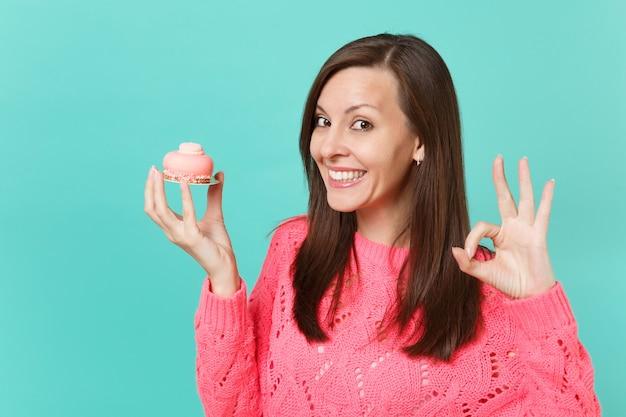 Улыбаясь привлекательная молодая женщина в вязаном розовом свитере, показывая жест ок, держа в руке торт, изолированные на синем фоне бирюзовой стены студийный портрет. концепция образа жизни людей. копируйте пространство для копирования.