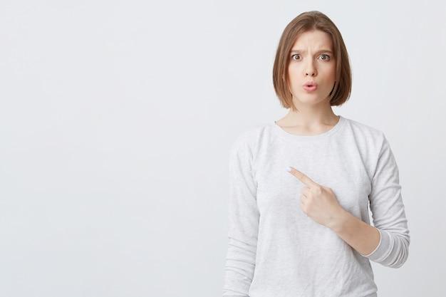 Улыбающаяся привлекательная молодая женщина в лонгсливе стоит и указывает на изолированную сторону