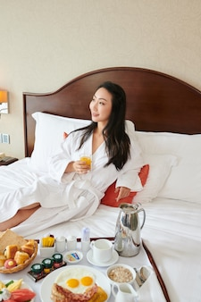 Smiling attractive young woman lying on bed and eating delicious tasty hotel breakfast